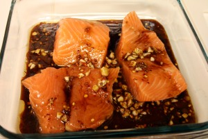 Three salmon fillets marinating.